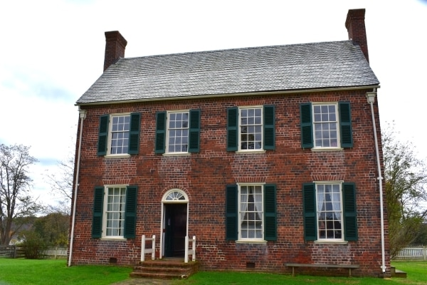 A two-story brick building serves as the Appomattox County Jail, with a door offset to the left, curtains on the downstairs windows and jail bars on the upper windows