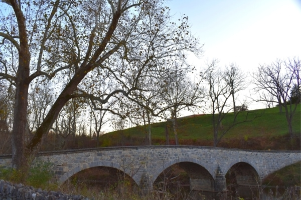 A three span stone arch bridge crosses Antietam Creek and is surrounded by tall hills