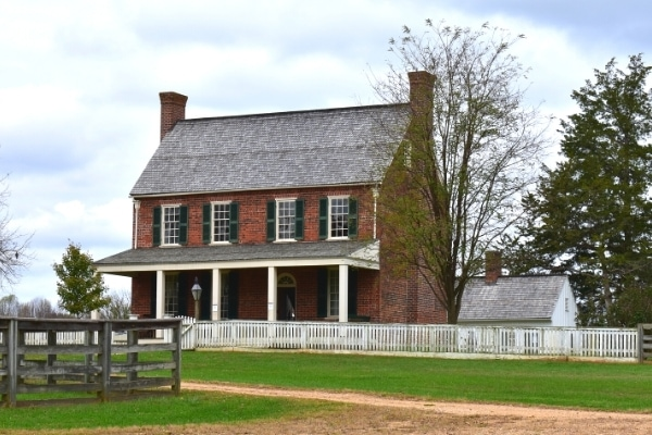 A two-story brick building with a covered front porch is surrounded by a white picket fence and sits at the dirt road crossroads in Appomattox Court House, Virginia