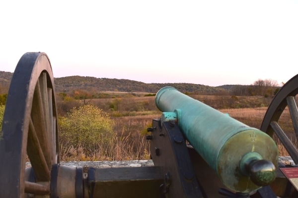 Looking down the side of a green-patinaed cannon aimed over the brown hillside in the distance