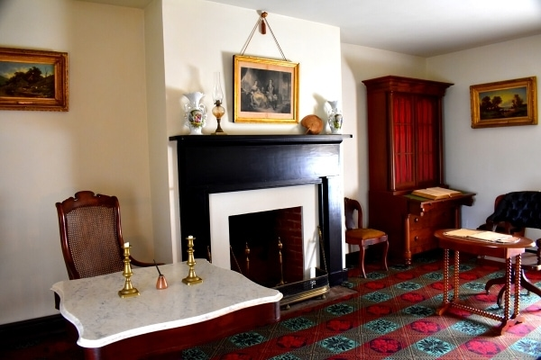 The parlor of the McLean House showcasing a marble desk and wooden desk used by generals to end the American Civil War
