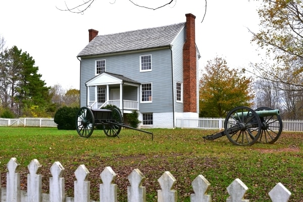 A simple blue gray three-story home with dual fireplaces, surrounded by a white picket fence and featuring a civil war cannon and supply cart in the front yard
