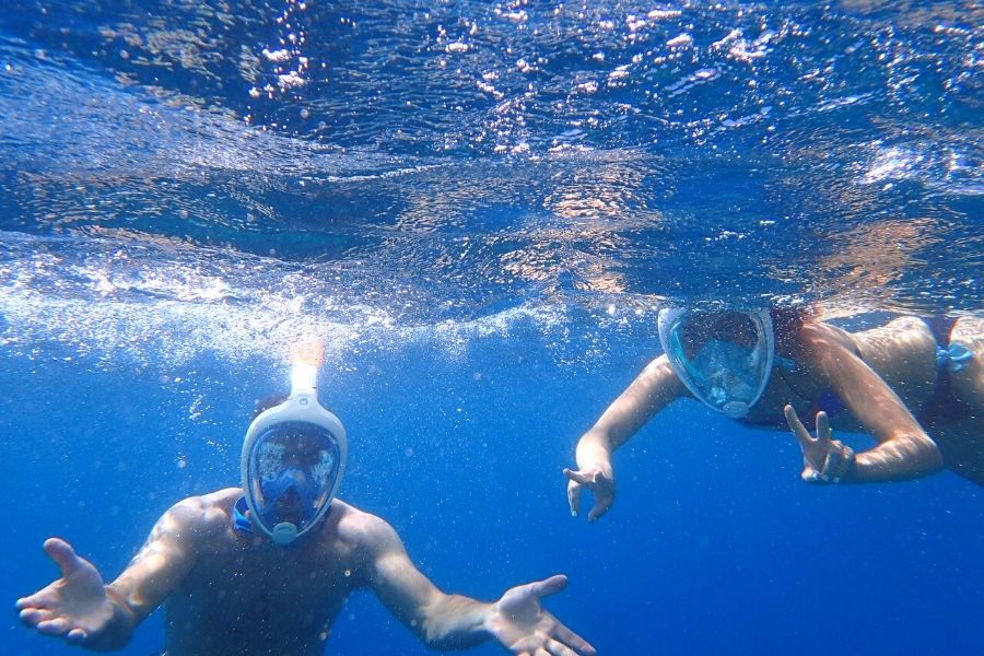 Two snorkelers using full-face snorkel mask in blue water