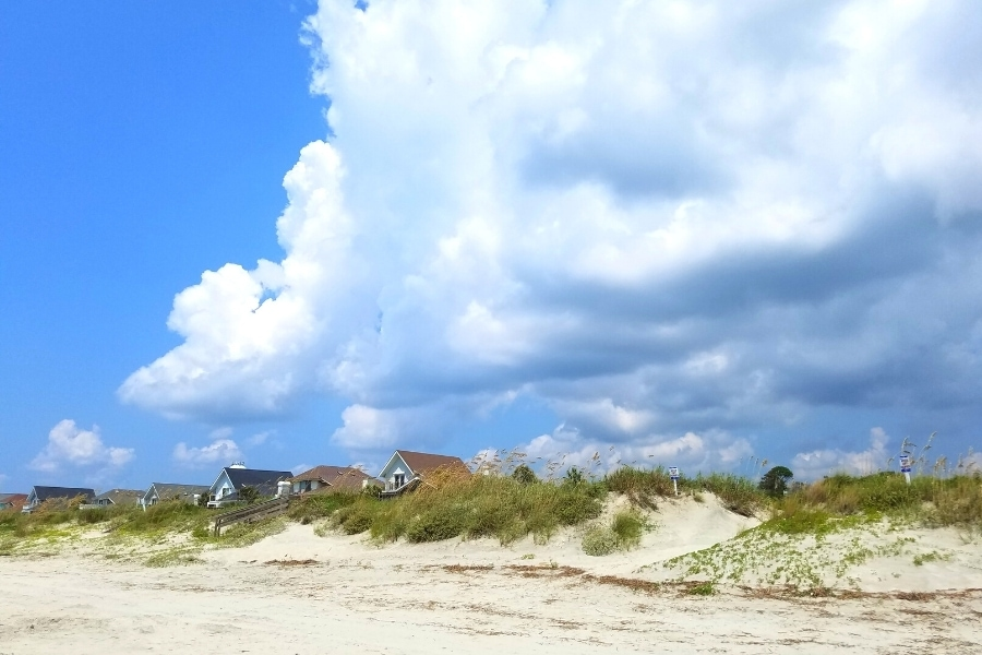 A storm front rolls in over the white sand dunes of Isle of Palms with beach homes in the background