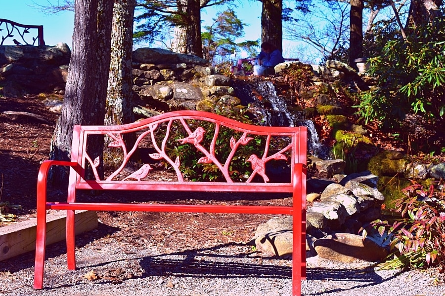 Red metal bench with bird latticing in front of a small waterfall on the grounds of the Blowing Rock site