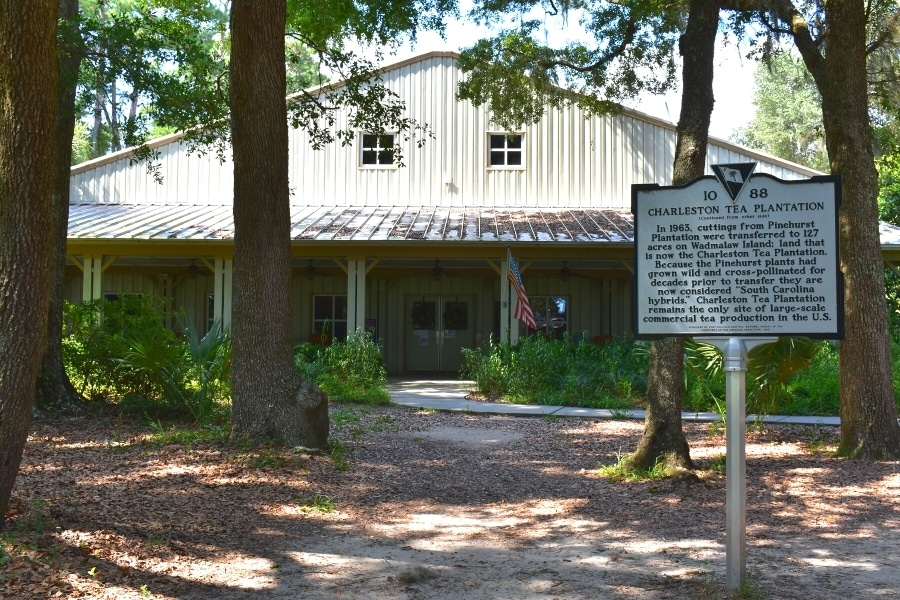 The Charleston Tea Garden's metal sided visitor center sits under the shade of trees with a historical marker out front