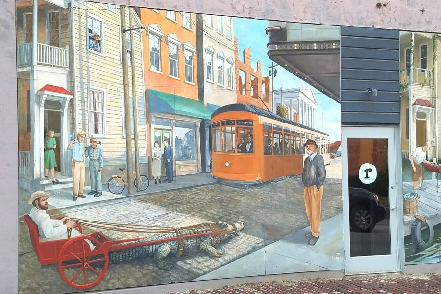 Colorful and whimsical mural on the side of a building showing a cable car and a gator pulled rickshaw
