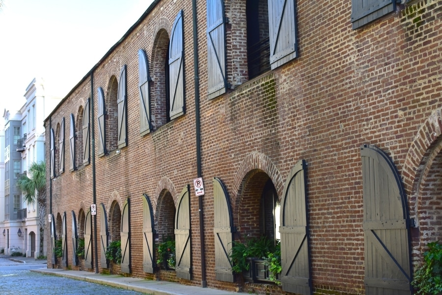 Brick building with arched windows and black wooden shutters flung open