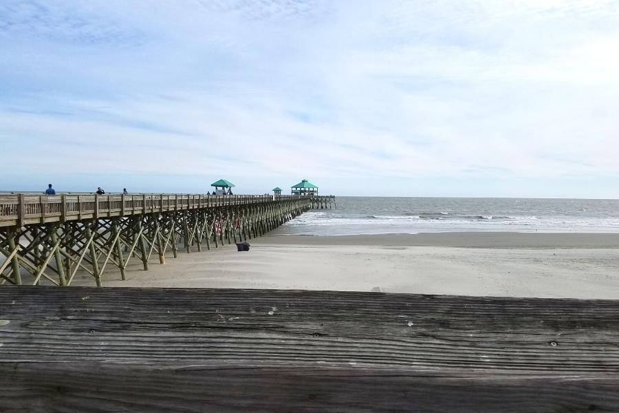 Wooden Folly Beach Pier extending across the sandy beach and into the ocean