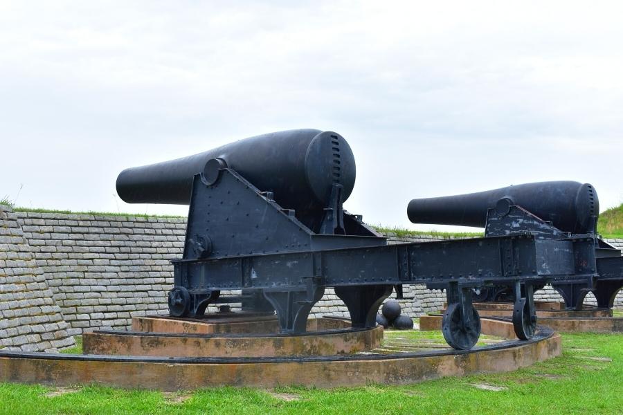 Black cannons on circular tracks peeking over a brick fort wall