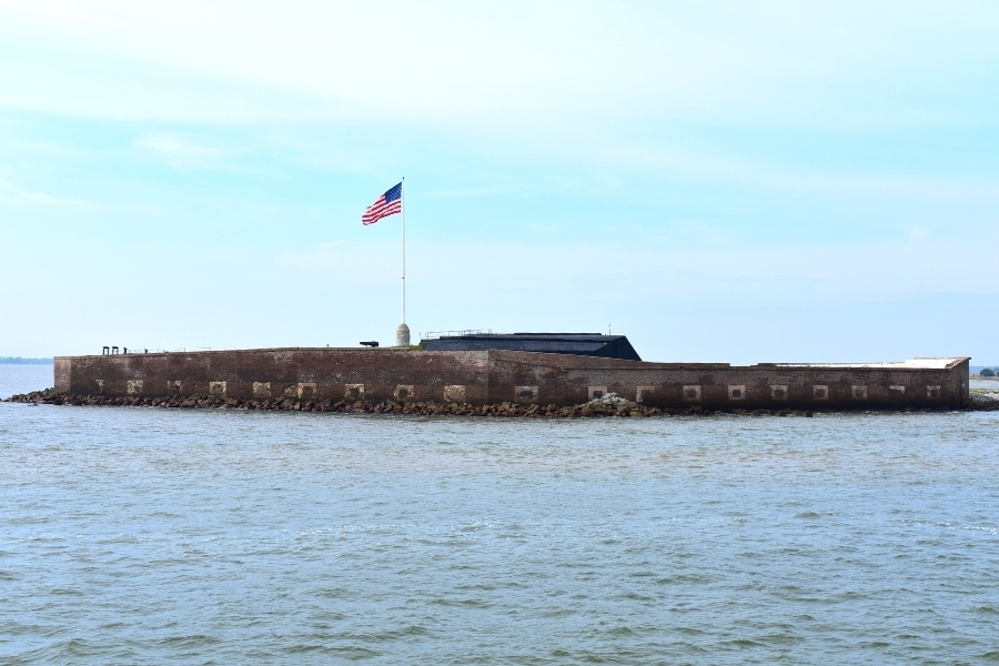 Brick fort surrounded by Charleston Harbor with an American flag overhead