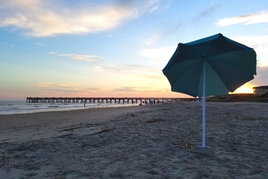 A blue and teal umbrella stands alone in the sand at Isle of Palms beach as the sun sets behind the pier in the distance