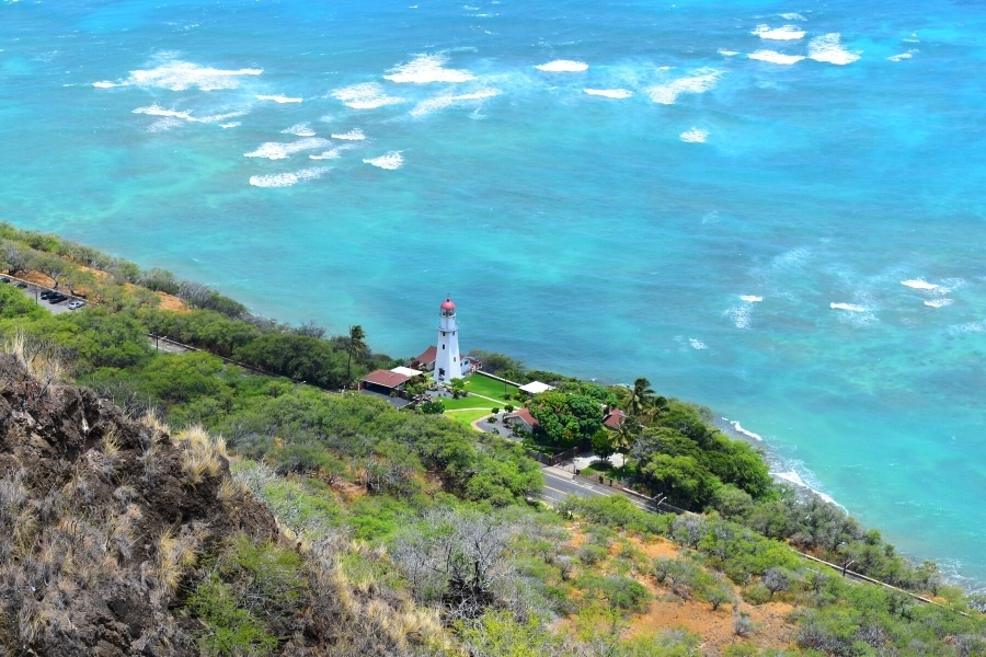 Lighthouse overlooking the various blue hues of the Pacific Ocean off the coast of Oahu