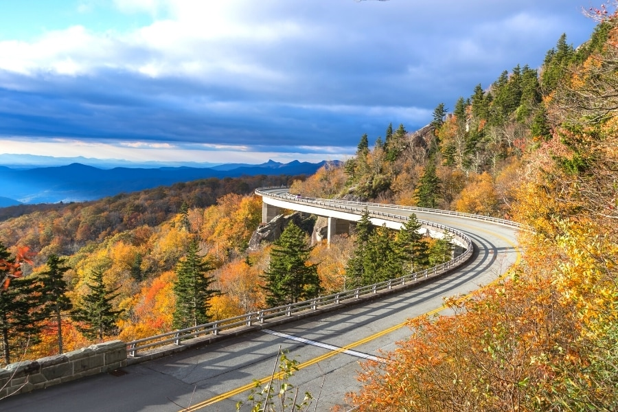 Linn Cove Viaduct on the Blue Ridge Parkway curves around the mountainside with the trees all orange for autumn