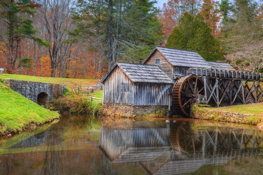 The old wooden Mabry Mill with waterwheel sits on the edge of a pond surrounded by a forest in fall