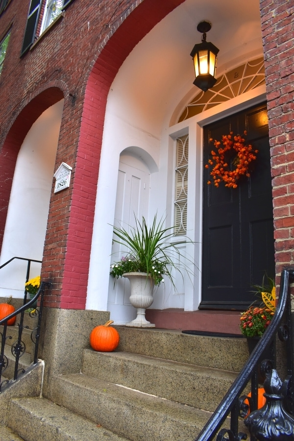 Townhome front porch in the McIntire Historic District are decorated for fall with pumpkins, mums, and an orange wreath