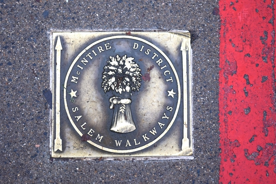 Metal plaque set in asphalt denoting the McIntire Historic District with and arrow and red stripe pointing the way for the walkway