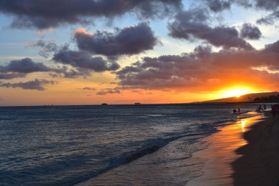 Vibrant orange sunset behind a mountain ridge, reflected across the beach in Oahu