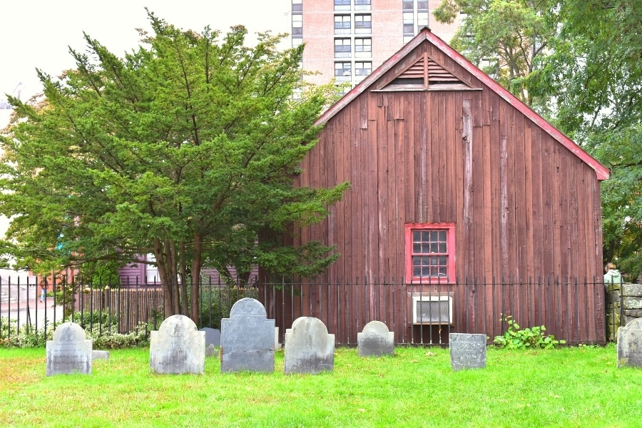 Headstones at Old Burying Point in Salem, MA with a large green tree and red building in the background