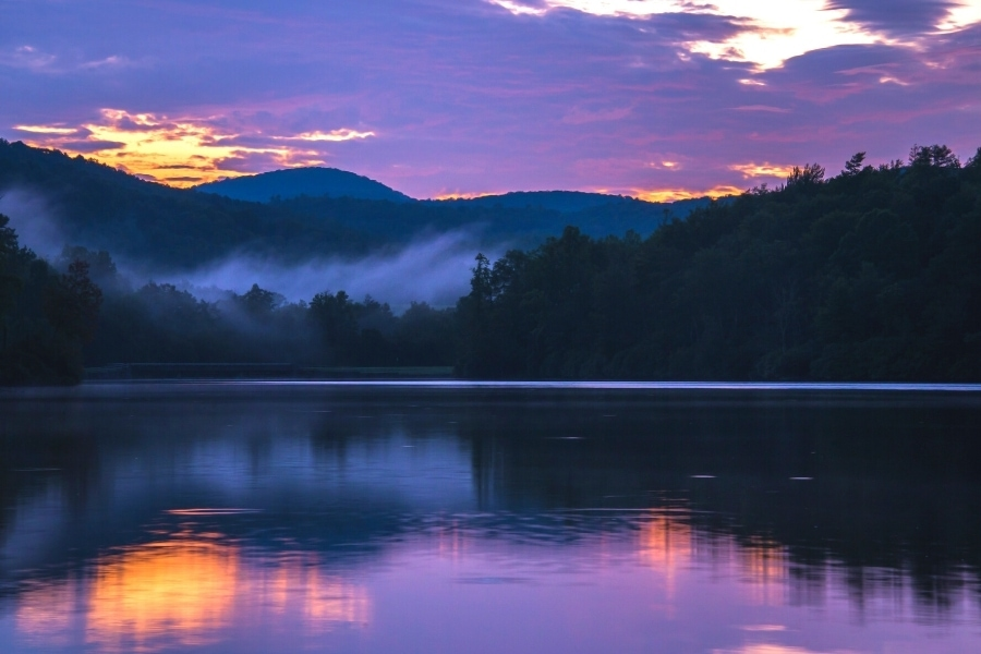 The cloudy sky turns purple as the sun rises behind the mountains surrounding Price Lake on Blue Ridge Parkway