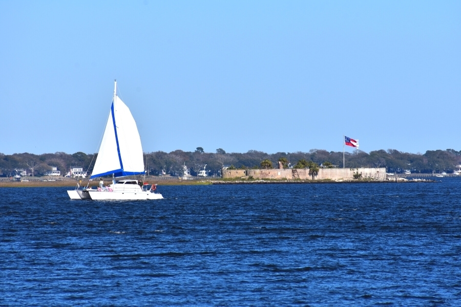 A white sailboat floats on a deep blue Charleston Harbor in front of Castle Pinckney
