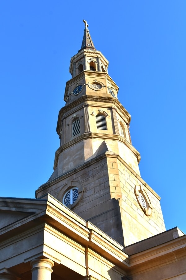Blonde stone church spire rises up into a clear blue sky