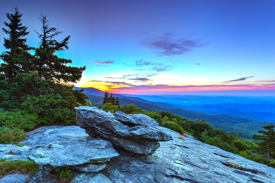 An orange sun rises behind the mountains, turning the dark blue sky orange, red, and purple over the Blue Ridge Mountains as seen from a rocky outcropping