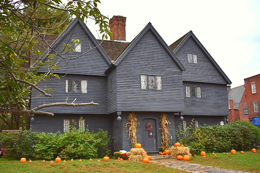 Large gray 3 story home, known as the Witch House, decorated for Halloween with pumpkins in the yard