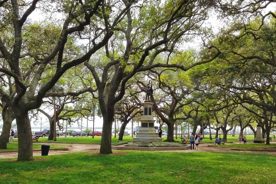 Green park full of southern live oaks with a monument in the middle